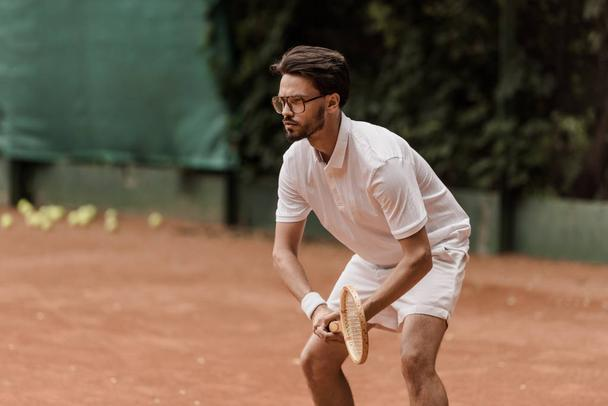 focused retro styled tennis player during game at tennis court - Photo, Image