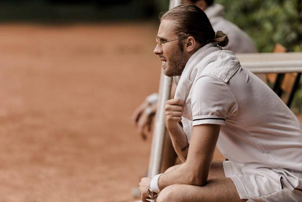side view of retro styled tennis player sitting on chair at tennis court and looking away - Photo, Image