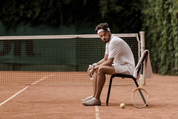 handsome retro styled tennis player sitting on chair with bottle of water at tennis court - Photo, Image
