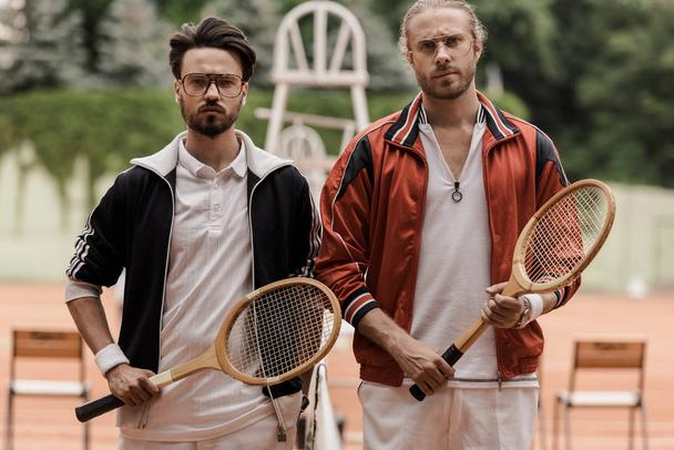 serious retro styled tennis players looking at camera at tennis court - Photo, Image