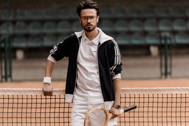 handsome tennis player looking at camera at tennis court and holding racket - Photo, Image