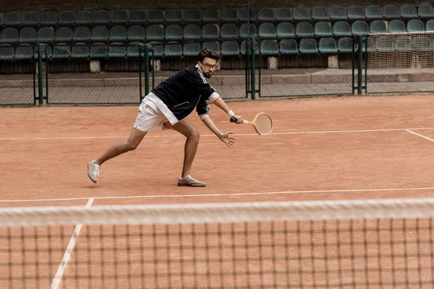 retro styled handsome man playing tennis with racket at tennis court - Photo, Image