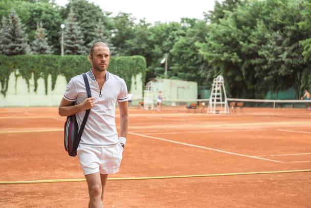 jogador de tênis bonito depois de treinar em quadra de tênis marrom   - Foto, Imagem
