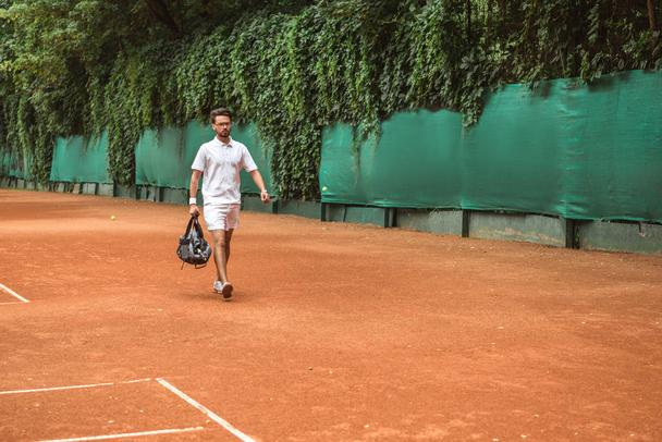 retro styled sportsman walking with bag after training on tennis court  - Photo, Image