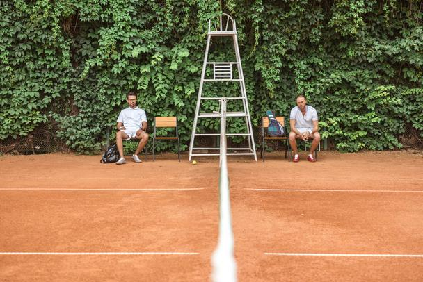 retro styled tennis players resting after training on chairs on brown court - Photo, Image