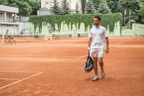 old-fashioned tennis player walking with bag after training on tennis court  - Photo, Image