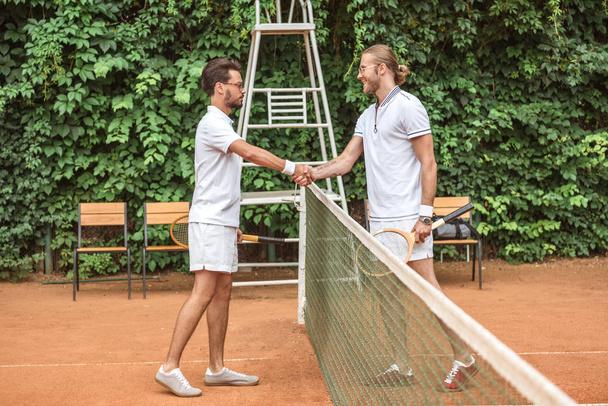 jogadores de tênis com raquetes de madeira apertando as mãos após o jogo no campo  - Foto, Imagem