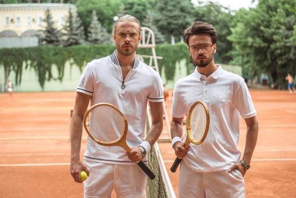 vážnou tenistů s dřevěnými pálkami a míč vystupují po zápase na hřišti  - Fotografie, Obrázek