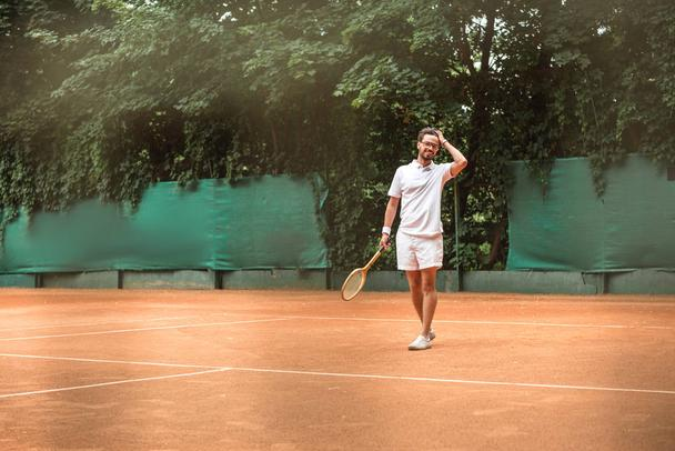 handsome tennis player with racket standing on tennis court - Photo, Image