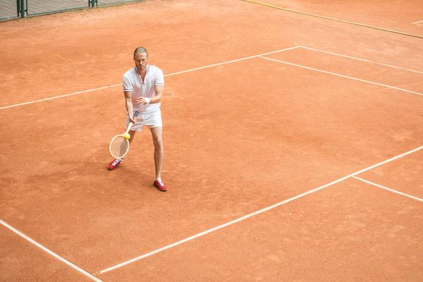 old-fashioned tennis player training with wooden racket and ball on brown court - Photo, Image