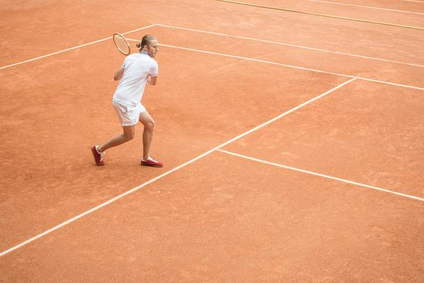 old-fashioned male tennis player with racket on brown tennis court - Photo, Image