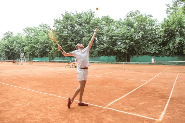 handsome tennis player with racket throwing ball on tennis court  - Photo, Image