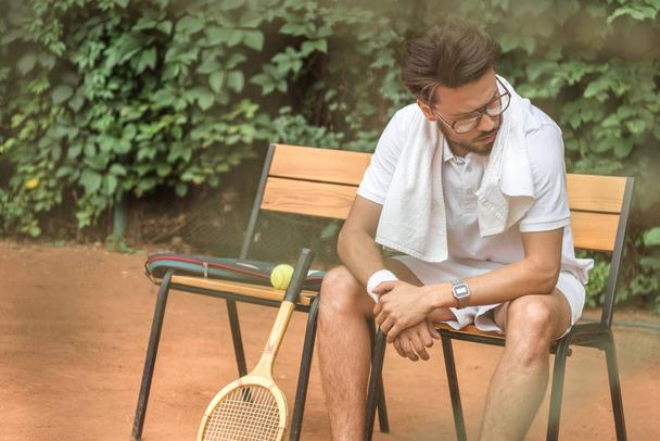 tired tennis player with towel and tennis racket resting on chair on tennis court  - Photo, Image