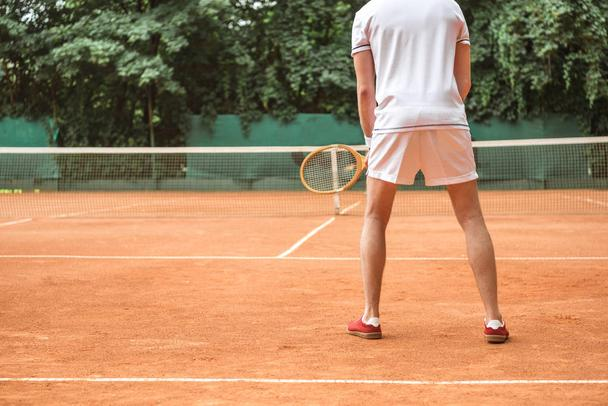 back view of tennis player with racket on tennis court with net - Photo, Image