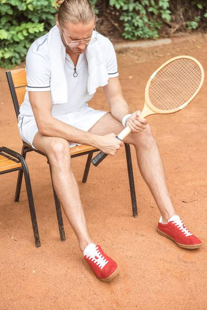 handsome tennis player with towel and tennis racket resting on chair on tennis court  - Photo, Image