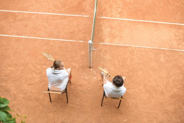 overhead view of tennis players with wooden rackets resting on court - Photo, Image