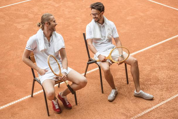 tennis players with towels and wooden rackets resting on chairs on brown court - Photo, Image