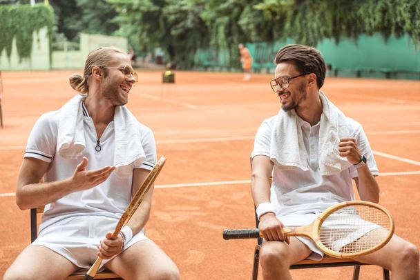 smiling tennis players with towels and wooden rackets resting on chairs  - Photo, Image