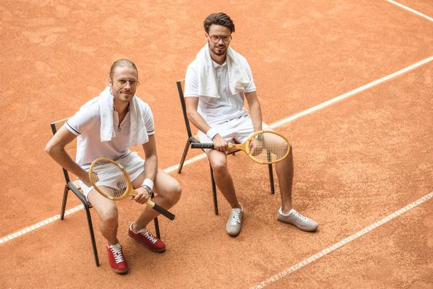tennis players with vintage wooden rackets resting on chairs  - Photo, Image