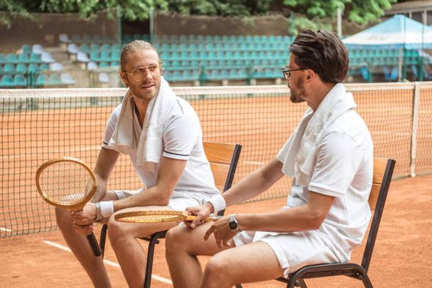 handsome athletic tennis players with retro wooden rackets resting on chairs  - Photo, Image