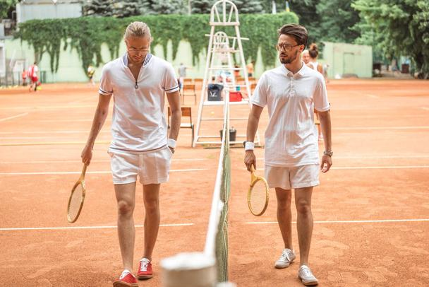 tennis players with wooden rackets walking near net on court - Photo, Image