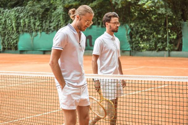 tennis players in white sportswear with wooden rackets walking near net on court - Photo, Image