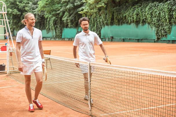 tennis players with wooden rackets walking after training near net on court - Photo, Image