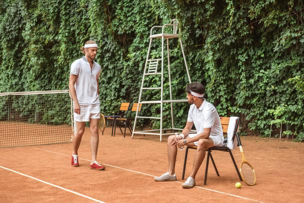old-fashioned tennis players in white sportswear on court - Photo, Image