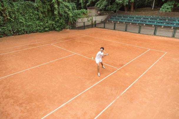man in white sportswear playing tennis with racket and ball on court - Photo, Image