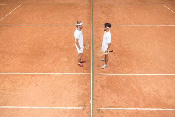 overhead view of tennis players in white sportswear with wooden rackets on court - Photo, Image