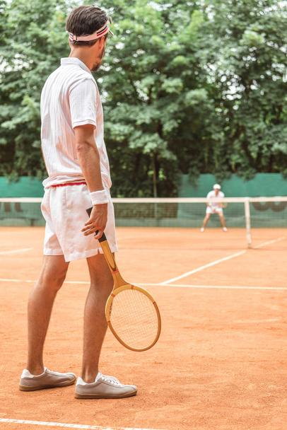 back view of man playing tennis with wooden racket on tennis court - Photo, Image