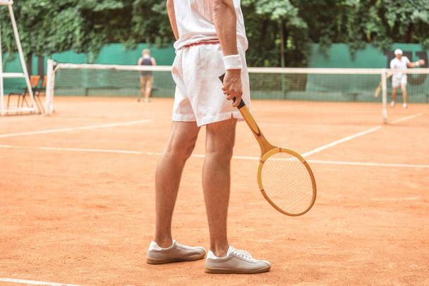 cropped view of tennis player holding retro wooden racket and standing on tennis court  - Photo, Image