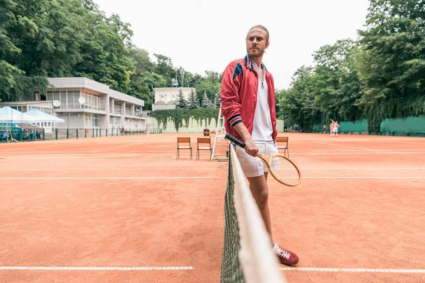 selective focus of handsome tennis player with racket standing at tennis net on court - Photo, Image