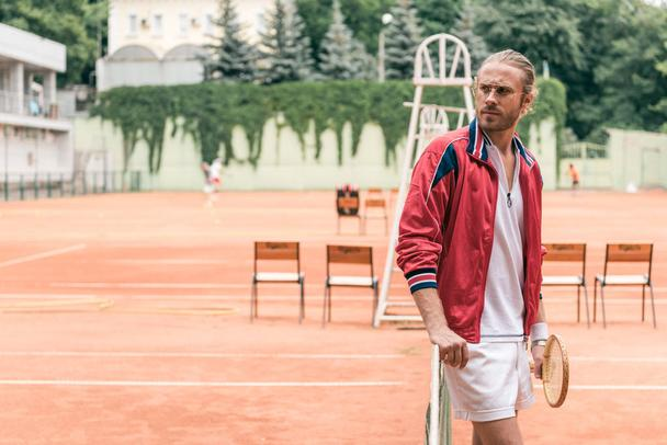 handsome caucasian tennis player with racket standing at net on tennis court - Photo, Image