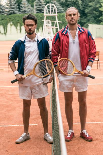 retro styled friends with wooden rackets posing on tennis court with net - Photo, Image