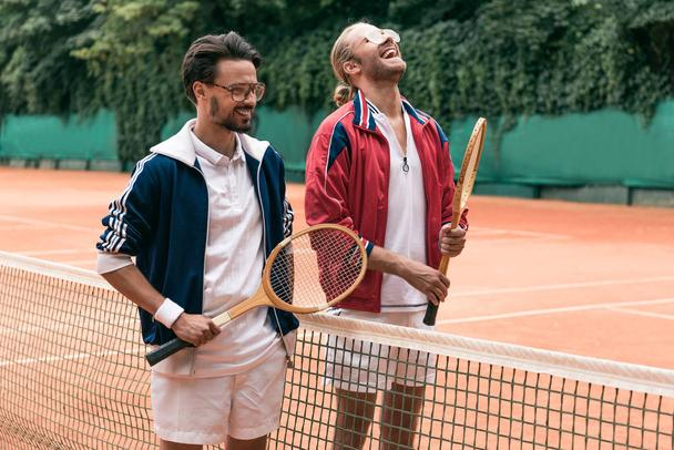 laughing retro styled friends with wooden rackets on tennis court with net - Photo, Image
