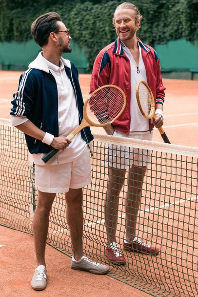 smiling friends with wooden rackets walking on tennis court with net - Photo, Image