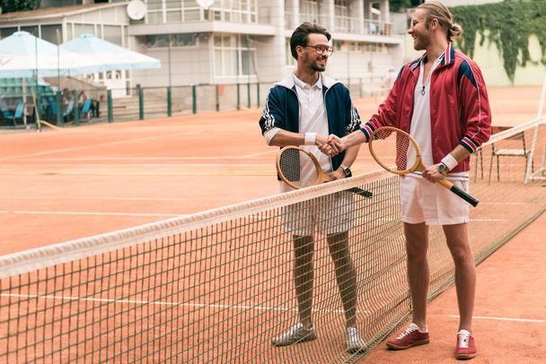 friends with wooden rackets shaking hands on tennis court with net - Photo, Image