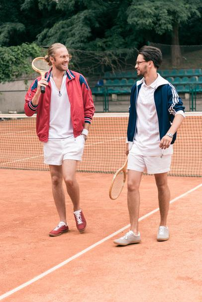 cheerful sportive friends with wooden rackets walking on tennis court - Photo, Image