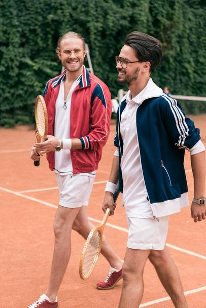 smiling retro styled friends with wooden rackets walking on tennis court - Photo, Image
