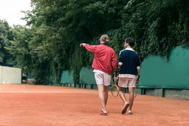 back view of retro styled friends with wooden rackets walking on tennis court - Photo, Image
