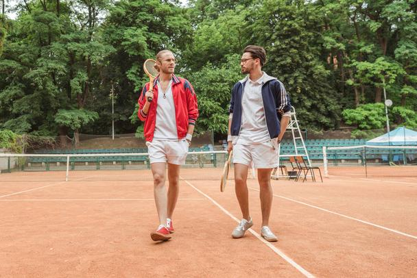 retro styled friends with wooden rackets walking on tennis court - Photo, Image