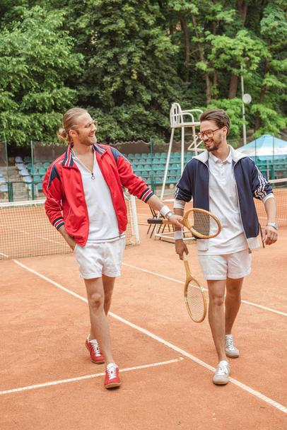 smiling friends with wooden rackets walking on tennis court - Photo, Image