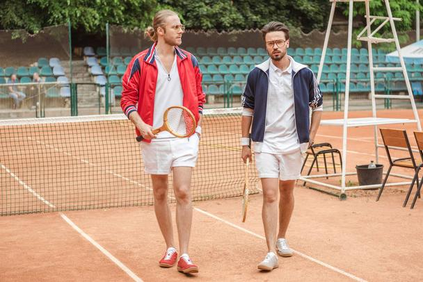 friends with wooden rackets walking on tennis court - Photo, Image