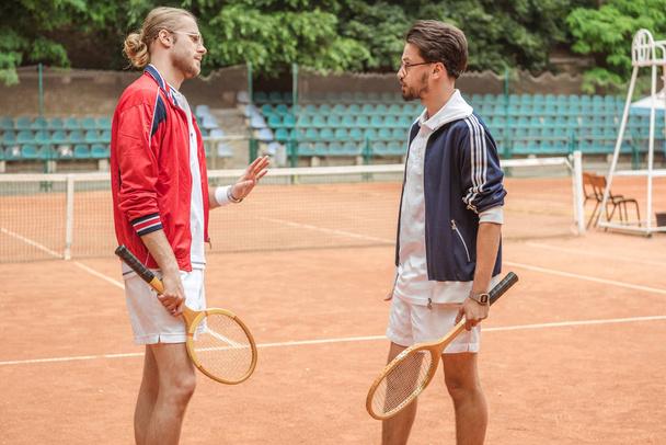 muži s dřevěnými raketami konfliktní na tenisový kurt - Fotografie, Obrázek