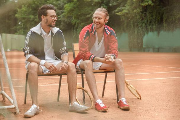happy sportive friends with wooden rackets sitting on chairs on tennis court - Photo, Image