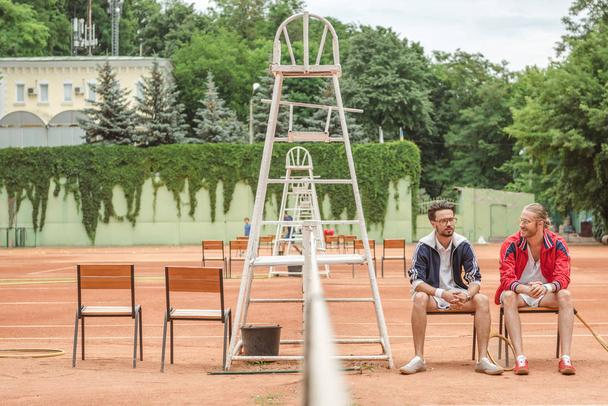 athletic friends with wooden rackets sitting on chairs on tennis court - Photo, Image
