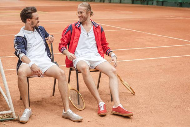 happy friends with wooden rackets sitting on chairs on tennis court - Photo, Image