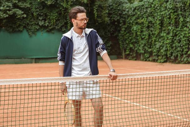 handsome tennis player with racket standing at net on tennis court - Photo, Image
