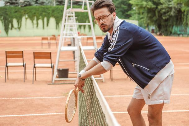 retro styled tennis player with wooden racket leaning on tennis net on court - Photo, Image
